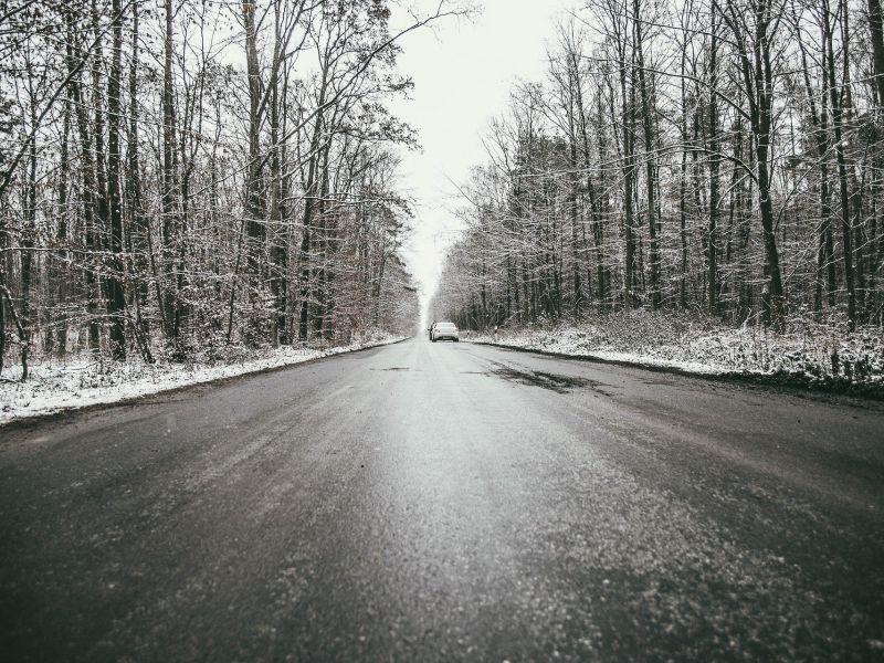 Na zdjęciu oblodzona nawierzchnia drogi podczas przymrozku. Po bokach drogi obśnieżone drzewa (las)