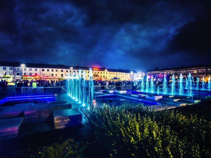 Zdjęcie pl. Kościuszki, wykonanane nocą. Granatowe niebo, widoczne podświetlone na niebiesko fontanny i w tle sylwetki ludzi
