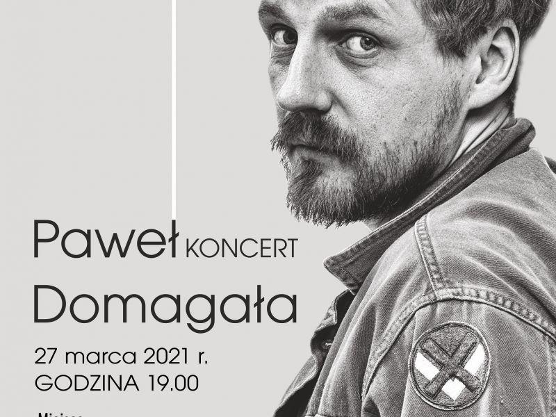Na zdjęciu plakat koncertu Pawła Domagały w Arenie Lodowej. Na zdjęciu artysta w kurtce jeansowej, obok informacje o koncercie