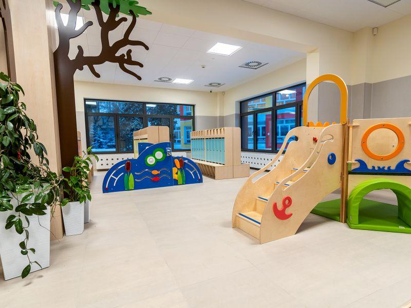 pokój z oknami kwiatami donicach oraz  szafki na ubrania i drewniany mini plac zabaw