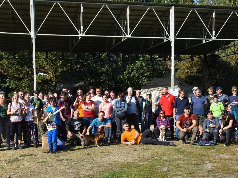 Na zdjęciu widać liczną grupę ludzi stojących pod zadaszeniem hangaru w Skansenie Rzeki Pilicy. To uczestnicy zlotu, w tle grupki stojących ludzi zabytkowe pojazdy z II w.ś.