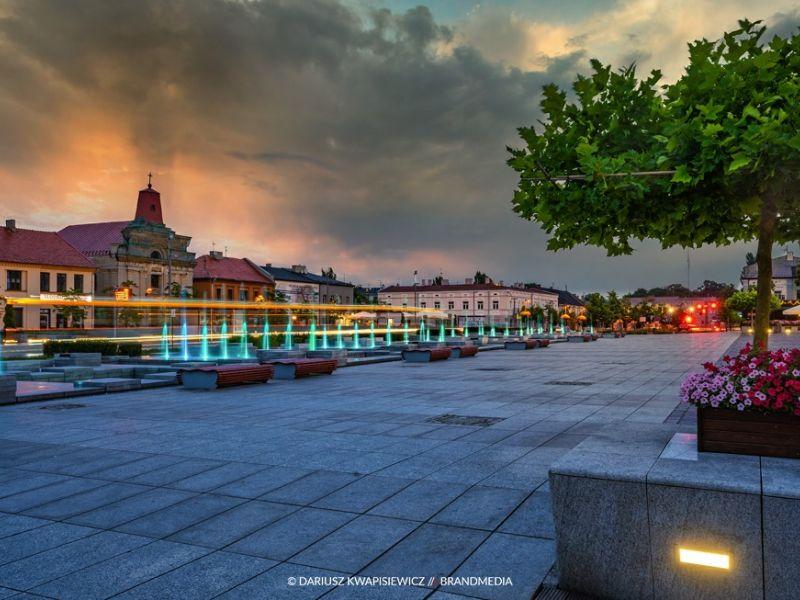 zdjęcie przedstawia plac Kościuszki wieczorem kolorowe fontanny, kwiaty w donicach, drzewo oraz dużo żółtych świateł