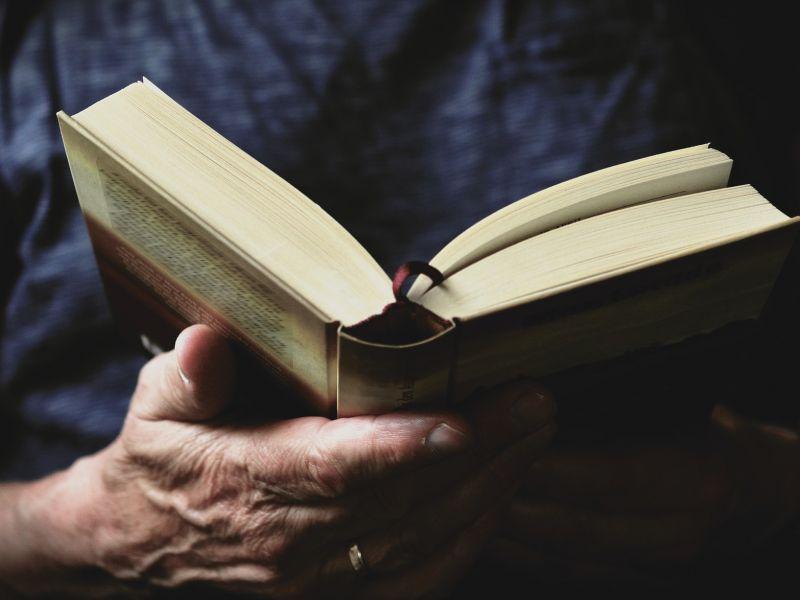 Na zdjęciu zbliżenie postaci trzymająćą w ręku książkę podczas czytania