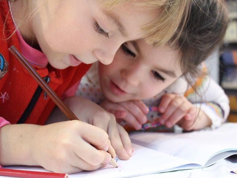 Dwoje dzieci pochyla się nad zeszytem, jedno trzyma brązową kredkę