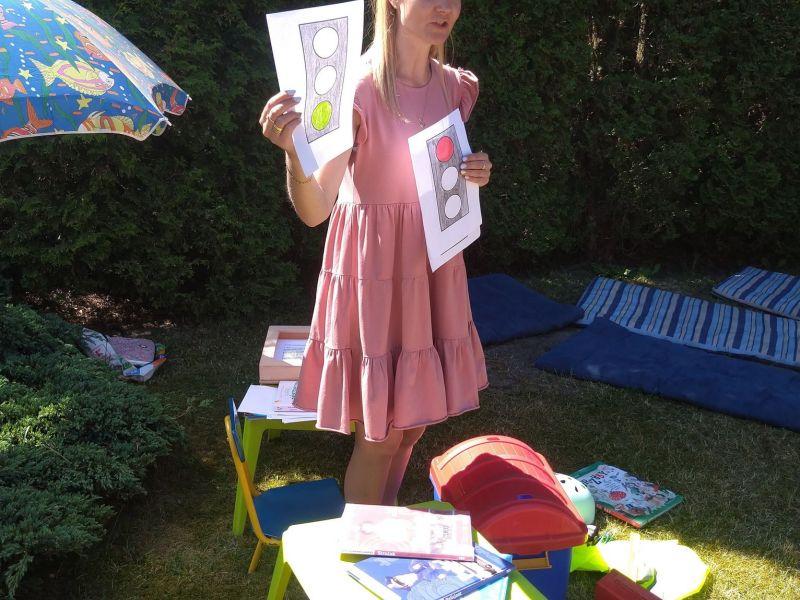 Na zdjęciu pracoiwnica MBP podczas zajęć bibliotecznych w przedszkolu na temat bezpiecznych wakacji. Bibliotekarka pokazuje dzieciom rysunek sygnalizacji świetylnej i tłumaczy zasady przechodzenia po pasach dla pieszych