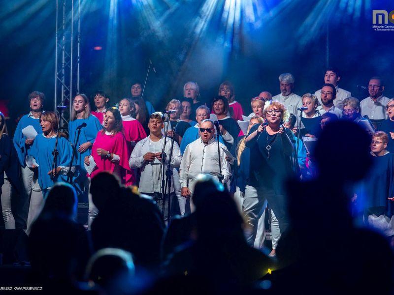 zdjęcie przedstawia śpiewajacych ludzi na scenie podczas koncertu  zrealizowanego w ramach projektu Rozśpiewaliśmy Tomaszów