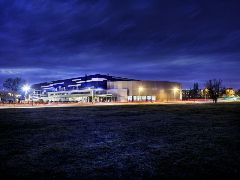 Nocne zdjęcie Areny Lodowej, granatowe niebo, ciemna trawa, w tle podświetlony, niebieski budynek Areny