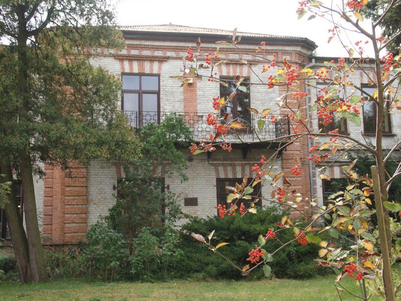 Na zdjęciu budynek z biało-czerwonej cegły, przed nim krzewy i drzewa.