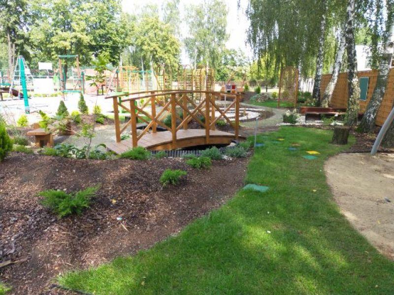 Na zdjęciu widoczny ogród sensoryczny, zielona trawa, mostek i krzewy