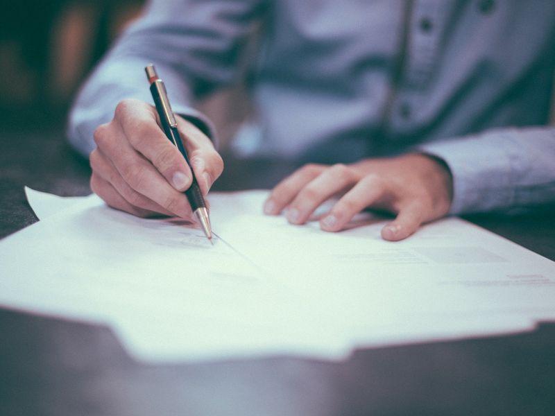Na zdjęciu osoba wypełniająca ankietę, zbliżenie kartki, rak trzymających długopis i formularza ankiety
