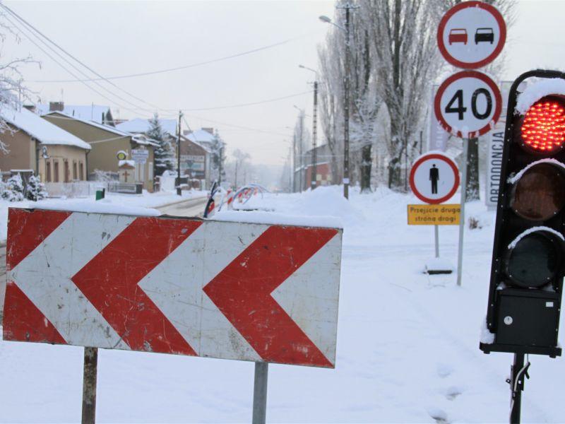 Na zdjęciu remont drogi dw 713, na pierwszym planie barierka ostrzegawcza, tymczasowa sygnalizacja świetlna do ruchu wahadłowego oraz oznaczenie znakami drogowymi