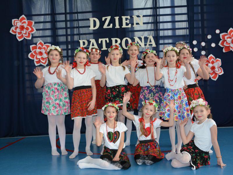 Na zdjęciu dzieci w wianuszkach i baiło-czerwonych koszulkach i sukienkach podczas Dnia Patrona w SP nr 3