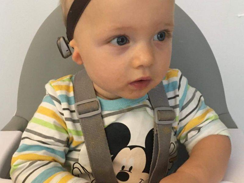 Na zdjęciu jest Jaś - mały chłopiec z brązową opaską na głowie, w bluzce w kolorowe paski, z myszką Miki