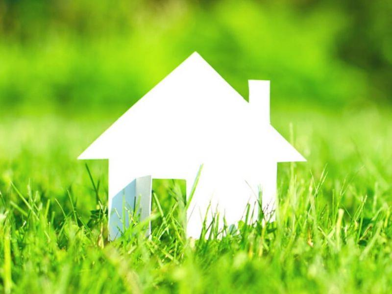 Na zdjęciu papierowy domoek stojący na trawie. Domek biały, trawa jaskrawo zielona