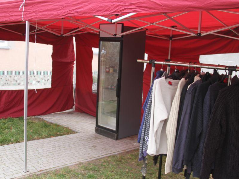 czerwony namiot w środku lodówka oraz wieszak z ubraniami