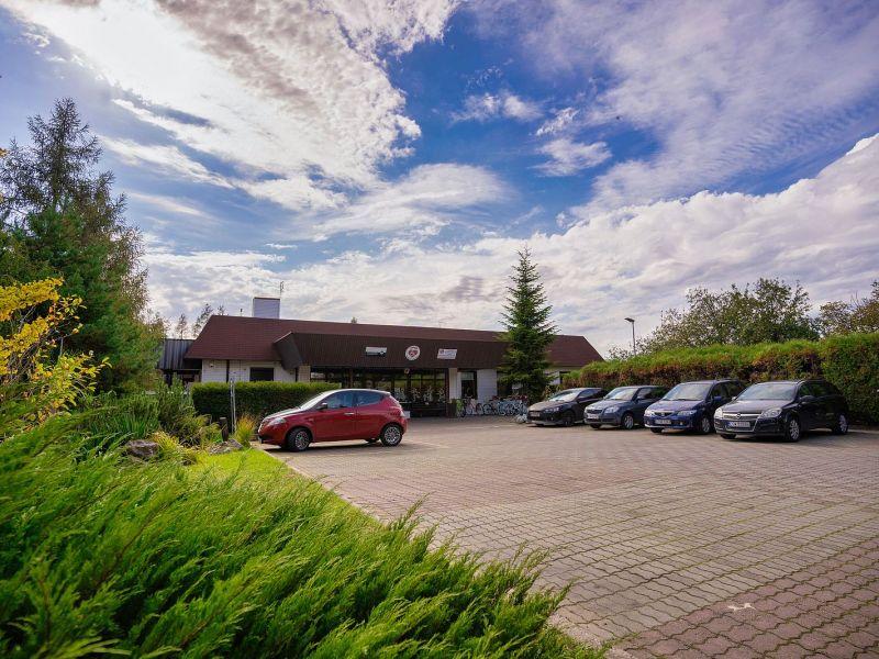 Z lewej strony zielona trawa i krzewy, z prawej kostka brukowa i samochody. W tle niski budynek na tle niebieskiego nieba z chmurami