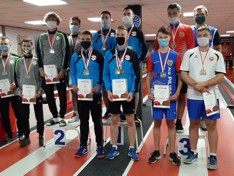 Na zdjęciu wiocznych jest 13 mężczyzn, trzech stoi na podium. Wszyscy mają dyplomy i medale