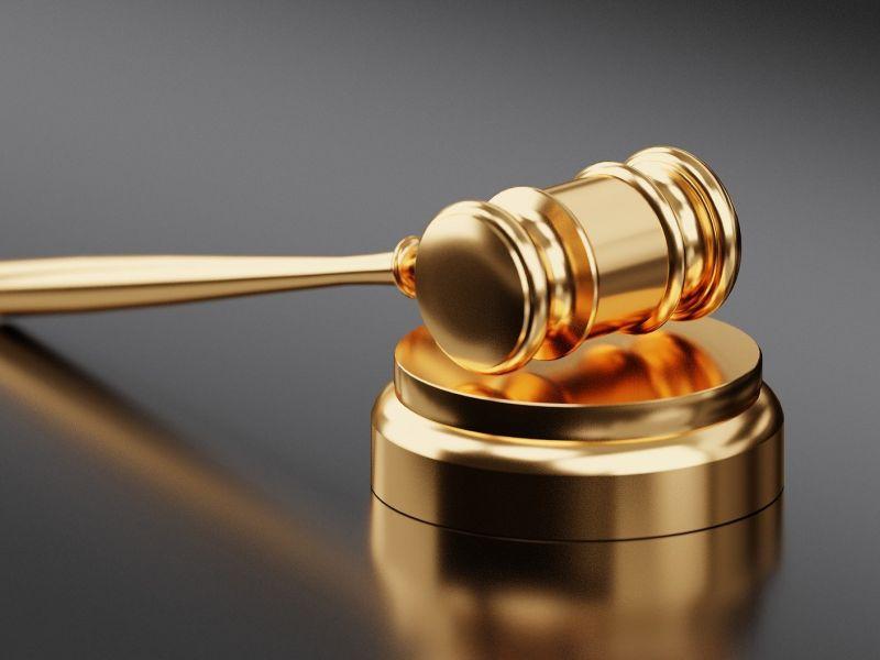 grafika przedstawiająca złoty młotek sędziowski na szarym tle