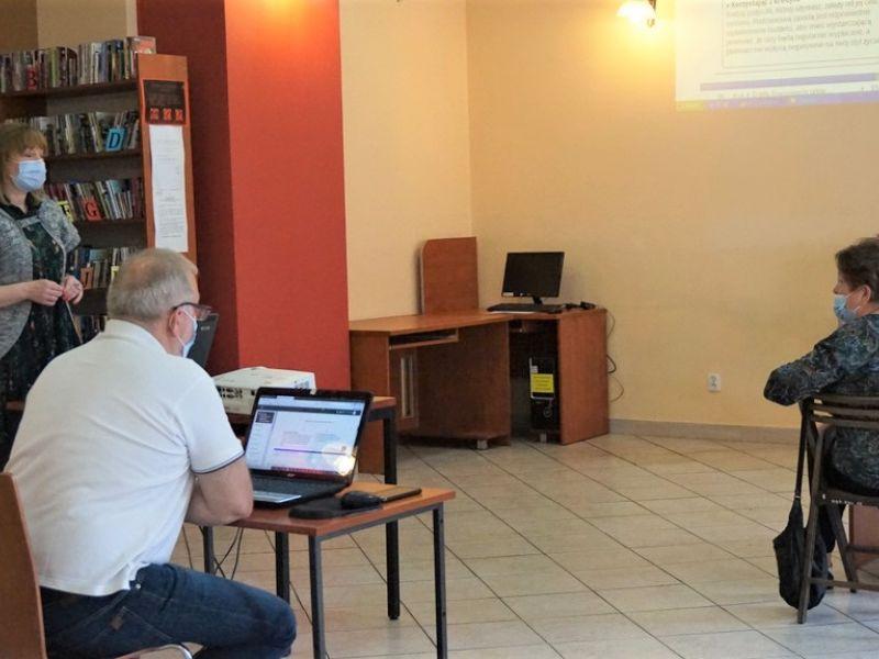 Na zdjęciu odsoby 55 plus korzystające z kursu organizowanego przez bibliotekę na temat finansów. Na fotografii osoby siedzą przy biurkach przed monitorami komputerów