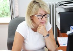 kobieta w białej bluzce siedząca przy biurku